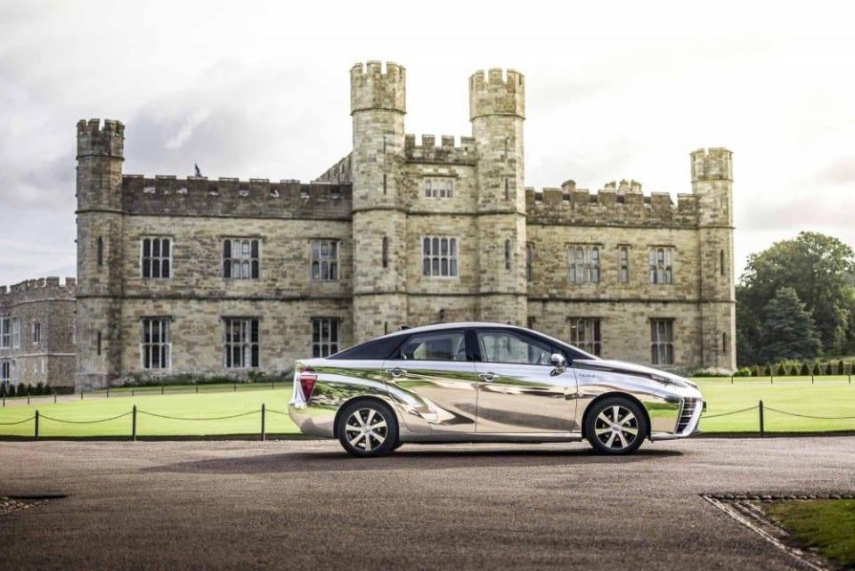 glimmend zilveren Toyota Mirai waterstofauto voor een oud kasteel