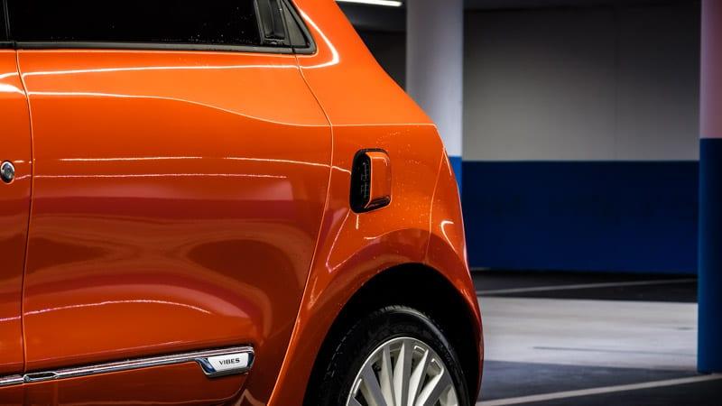 oranje Renault Twingo Electric links achter met luchtinlaat