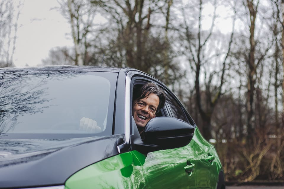 man steekt hoofd uit geopend bestuurdersportier groene Opel Mokka