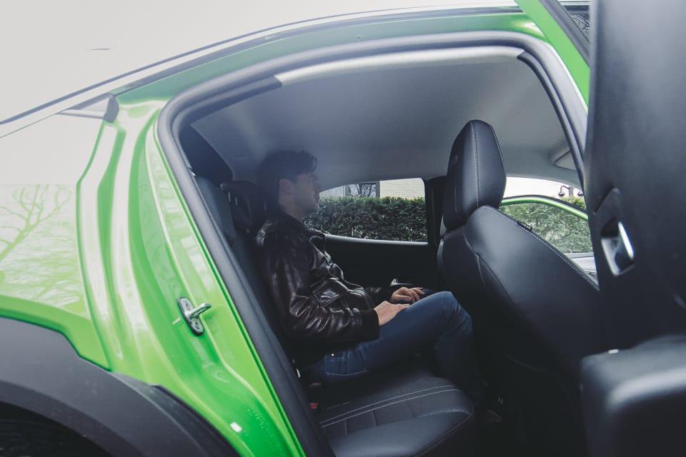 persoon zit op achterbank. Geopende achterdeur Opel Mokka-e