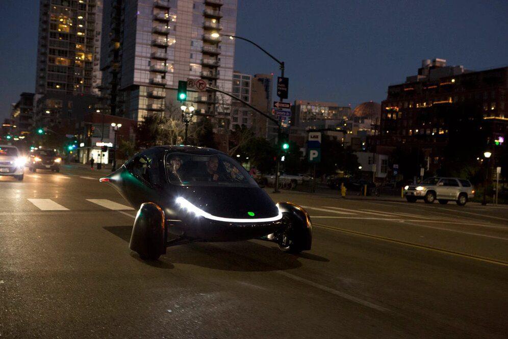 zwarte Aptera rijdt 's avonds door de stad