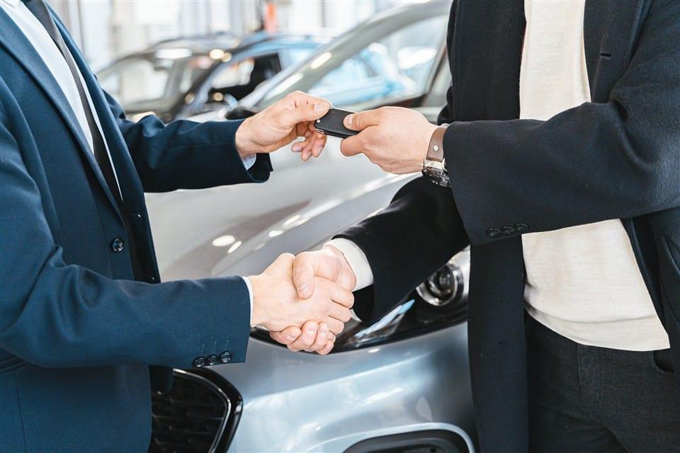 Autoverkoper geeft sleutel aan koper auto op de achtergrond