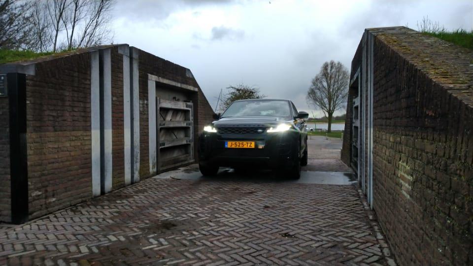 voorkant zwarte Range Rover Evoque tussen twee muren