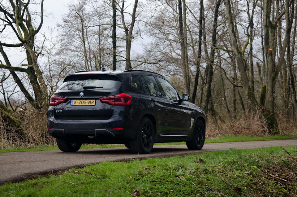 Rechter achterzijde BMW iX3 Shadowline, smalle asfaltweg, gras, bomen, mos, bos