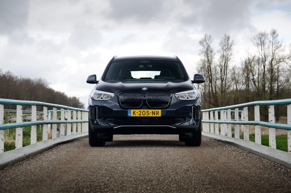 BMW iX3 Shadowline voorzijde, donkere lucht, imponerend, brug, hekjes