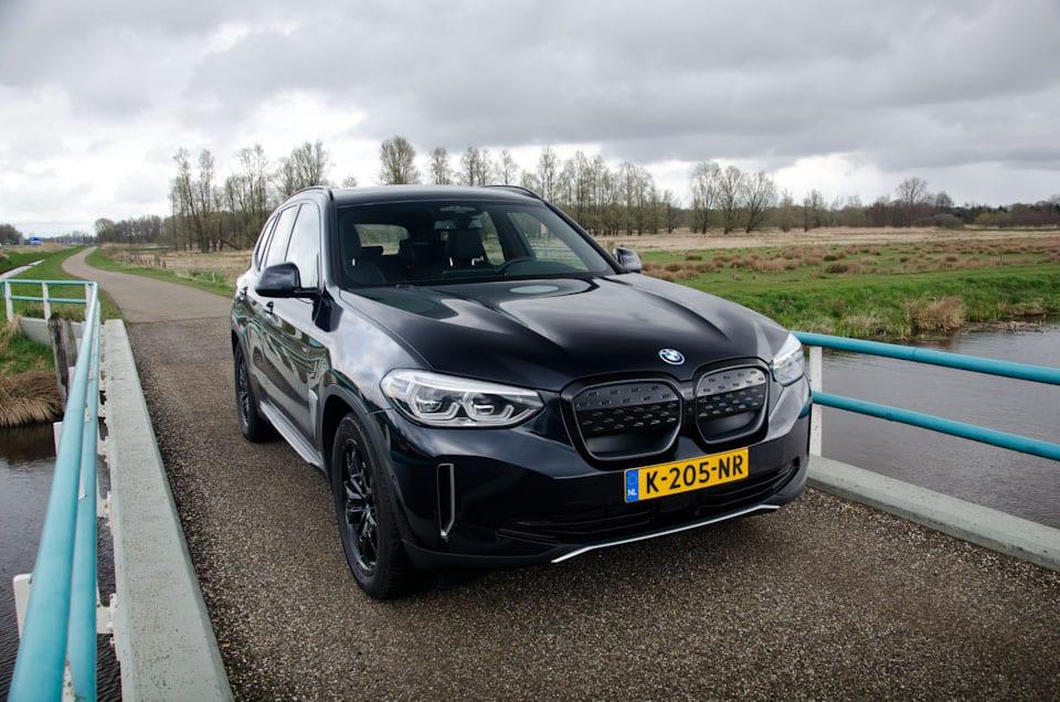 BMW iX3 Shadowline rechter voorzijde, donkere lucht, brug, hekjes