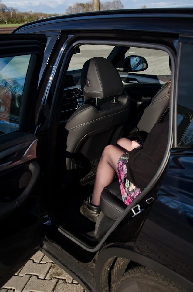 Zitpositie achterbank BMW X3, voorstoel, benen, knieën