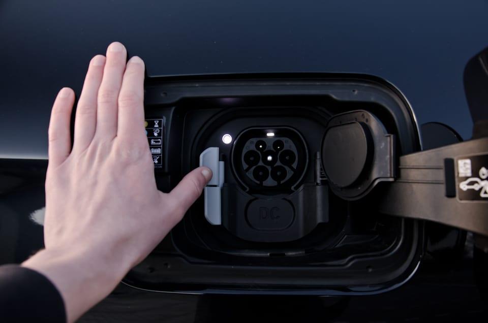 Hand, duim op drukknop, Mennekes laadaansluiting BMW iX3