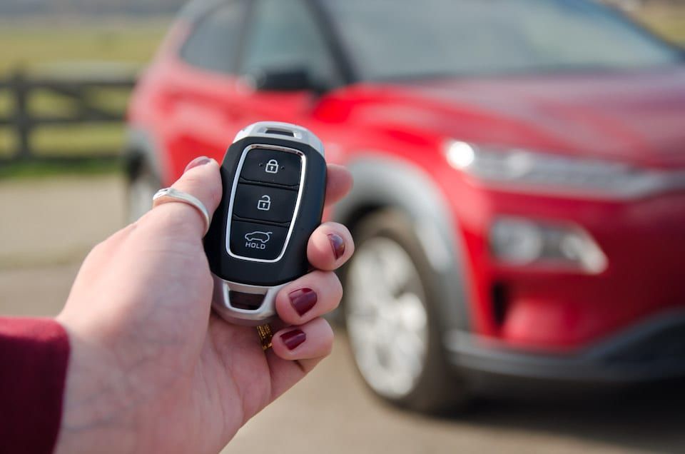 Hand met Hyundai autosleutel, auto vaag op de achtergrond, rode nagellak