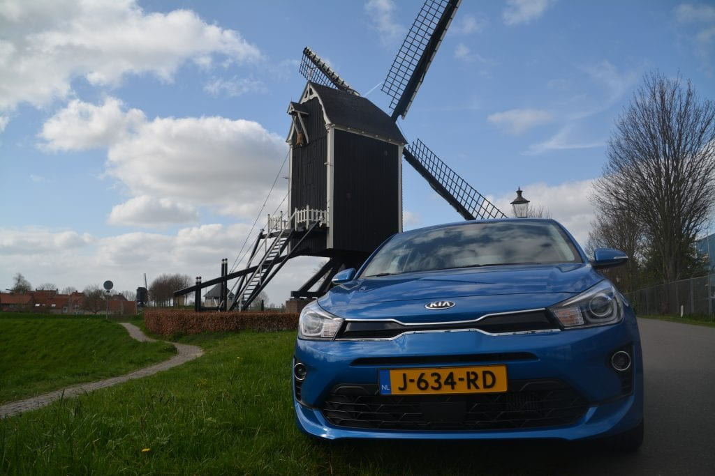 neus blauw Kia Rio met molen op de achtergrond