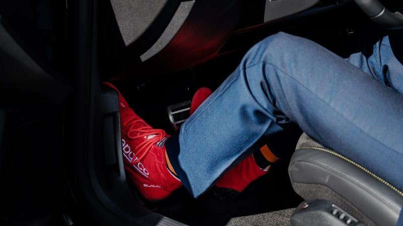 rode Sparco schoenen met gekleurde Happy Socks onder blauw kostuum rijdend in de auto