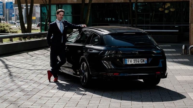 Joeri van Dam bij zwarte Peugeot 508 SW PSE achterkant