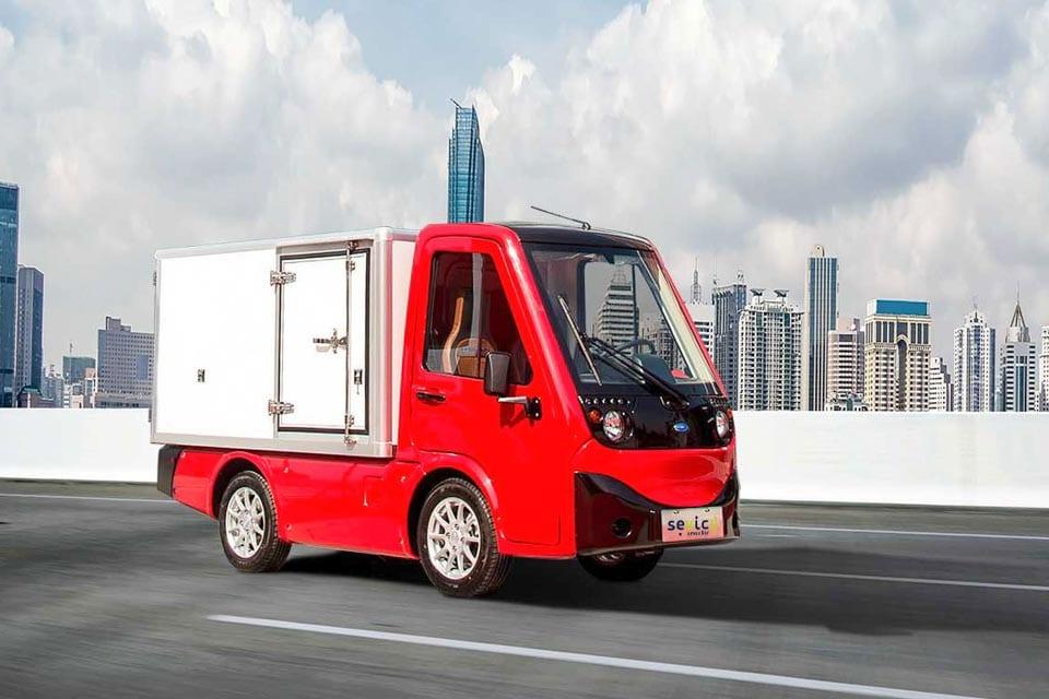 Sevic Cargo, elektrische bedrijfswagen, rood vrachtwagentje, skyline, wolkenkrabbers, elektrische mobiliteit welectric