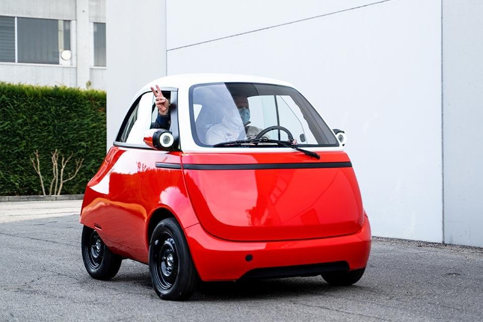 Microlino 1.0 prototype, rode bubblecar, hand uit het raam, bestuurder met mondkapje