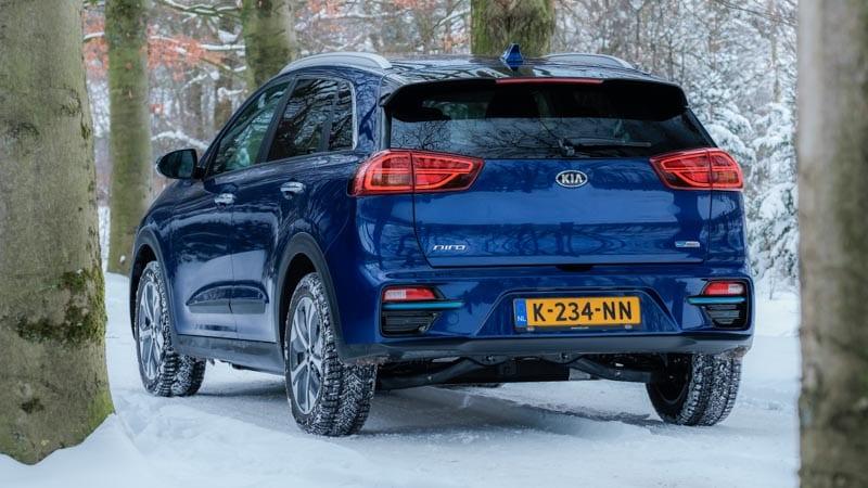 achterkant blauwe Kia e-Niro in de sneeuw