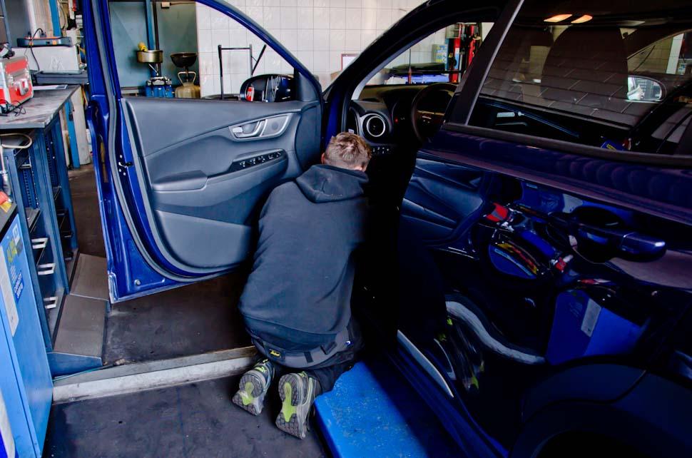 Garagemedewerker in opening voorportier Hyundai KONA Electric