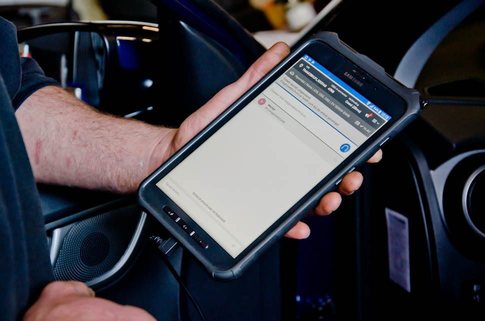Samsung device in de hand van garagist, State of Health check in proces