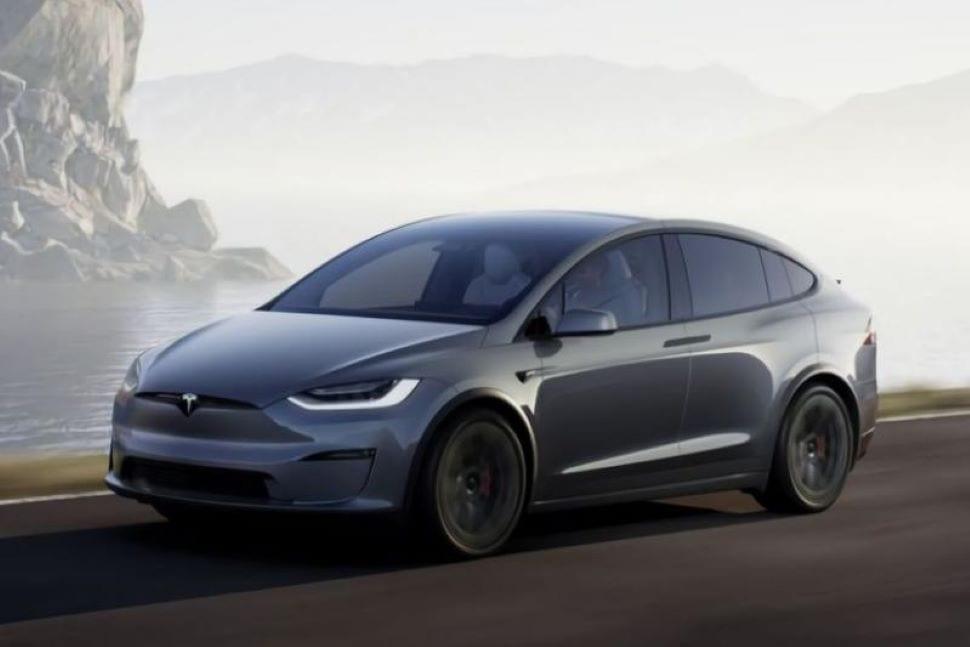 grijze Tesla Model X Plaid rijdend op de weg voor een meer