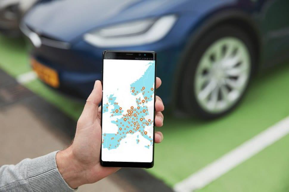 Telefoon met laadpas-app, weergave dekkingsgraad laadpalen in Europa, elektrische auto, Tesla Model X vaag op de achtergrond