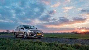 Hyundai i30 op dijkweg bij zonsondergang