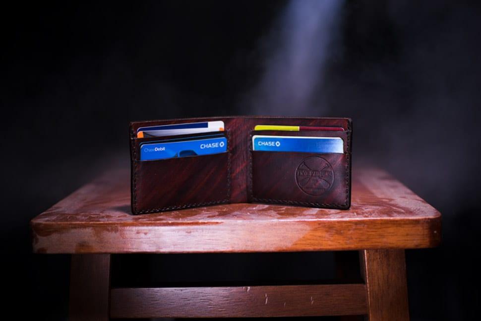 Portemonnee vol pasjes, laadpas tentoongesteld op een tafel, donkere achtergrond, portemonnee in spotlight