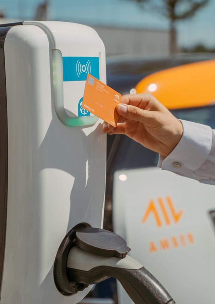 Contactloos betalen met de laadpas, bij een laadpaal, elektrische auto, oranje laadpas, laadkabel en stekker zichtbaar
