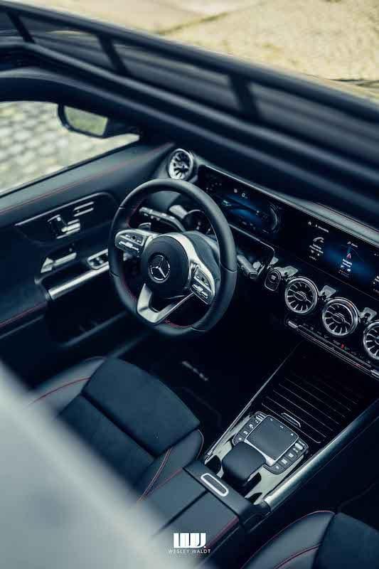 interieur van de Mercedes EQA, gefotografeerd door het dakraam, stuurwiel met Mercedes logo, verchroomde ventilatieroosters, transmissiekeuzehendel en touchpad