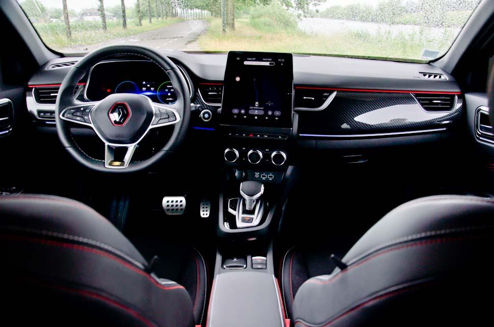 Interieur met rode details en accenten, display in middenconsole, Renault logo op stuur, doorkijk tussen twee voorstoelen