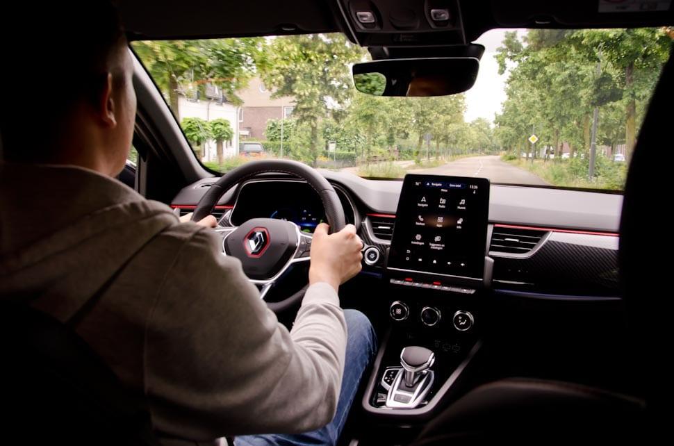 Renault Arkana interieur, persoon achter het stuur, rijdend