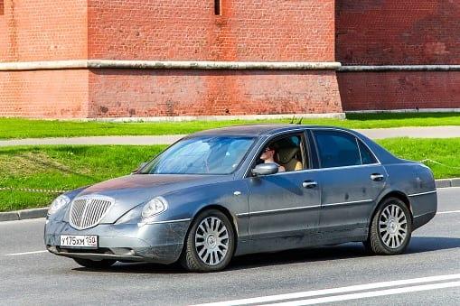 Voor- en zijaanzicht Lancia Thesis, grijze auto met Russisch kenteken, rode muur op de achtergrond