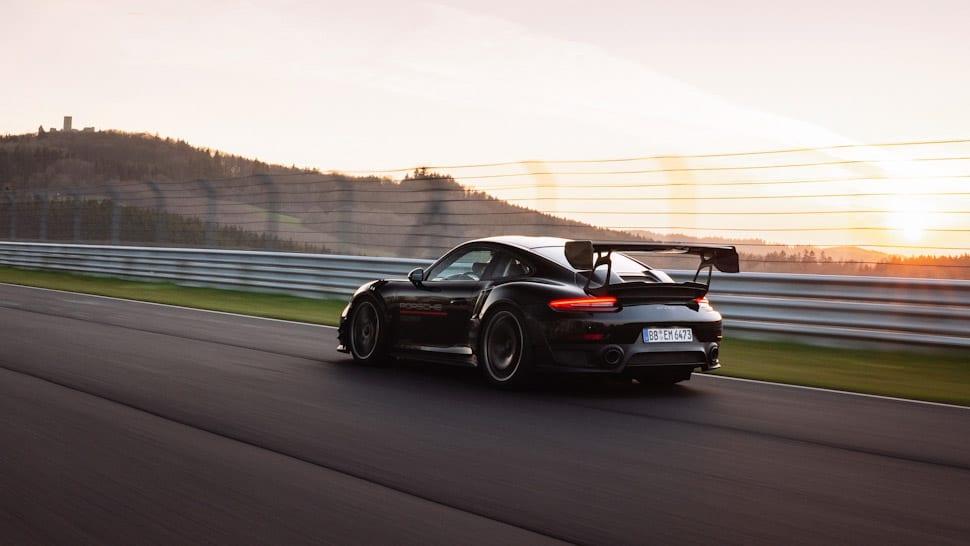 Linkerzijde achterzijde Porsche 911 GT2 RS MR, Manthey Racing, zwarte auto met grote spoiler, vleugel, Nürburgring Nordschleife, kasteel op berg