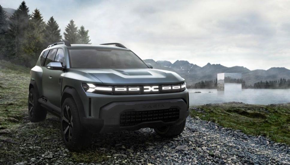 De Dacia Bigster met de nieuwe, robuuste styling, op grindpad, in natuurlijk landschap, meer, bergen, bos