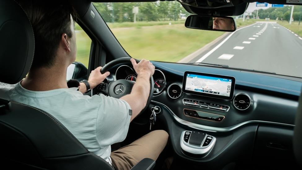 man rijdend met Mercedes EQV van achteren gefotografeerd