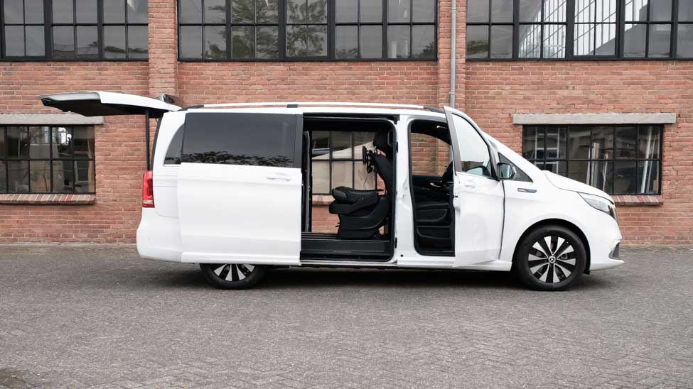 witte Mercedes EQV met open deuren en achterklep voor stenen gebouw