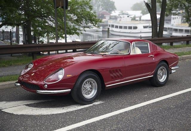 De Ferrari 275 GTB/C Speciale in het donker rood, geparkeerd op de normale weg bij een haven.