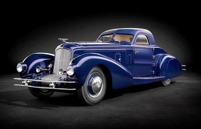 De luxe Deusenberg Model J in het donkerblauw, krachtig gefotografeerd.