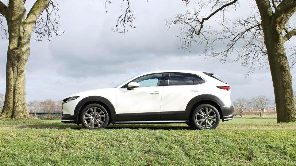Linkerzijde Mazda CX-30, witte auto op gras, tussen bomen, crossover, zwarte randen rondom wielkasten