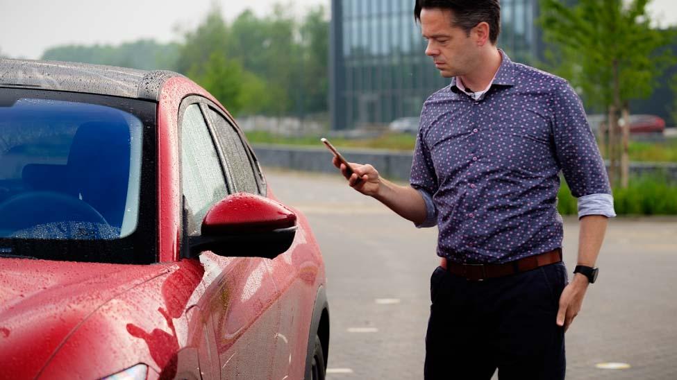 Persoon met telefoon in de hand, naast rode auto, FordPass app, Joeri van Dam